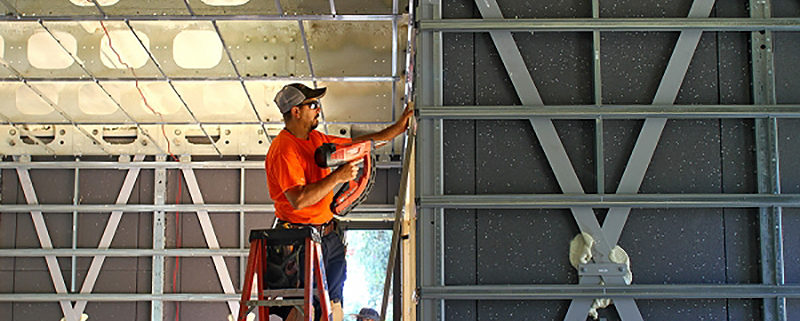 Palo Alto Online | Federico Hernandez, a carpenter with Wilkinson Construction, installs window supports in the BONE Structure house under construction on June 20. Photo by Veronica Weber.